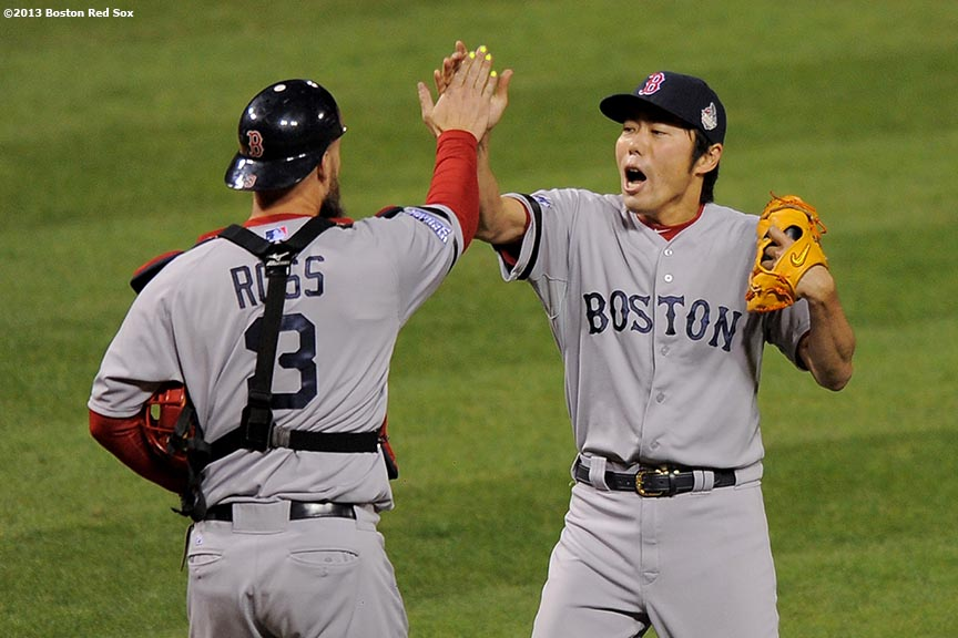 """Boston Red Sox pitcher Koji Uehara high fives catcher David Ross after recording the final out to defeat the St. Louis Cardinals 3-1 in game five of the 2013 World Series Monday, October 28, 2013 at Busch Stadium in St. Louis, Missouri."""