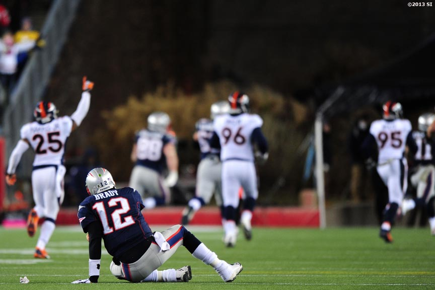 """New England Patriots quarterback Tom Brady reacts as Denver Broncos players celebrate after recovering a fumble Sunday, November 24, 2013 at Gillette Stadium in Foxborough, Massachusetts."""