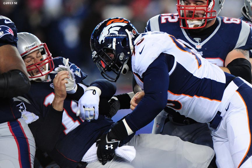 """Denver Broncos defensive end Derek Wolfe forces a fumble as he tackles New England Patriots quarterback Tom Brady Sunday, November 24, 2013 at Gillette Stadium in Foxborough, Massachusetts."""