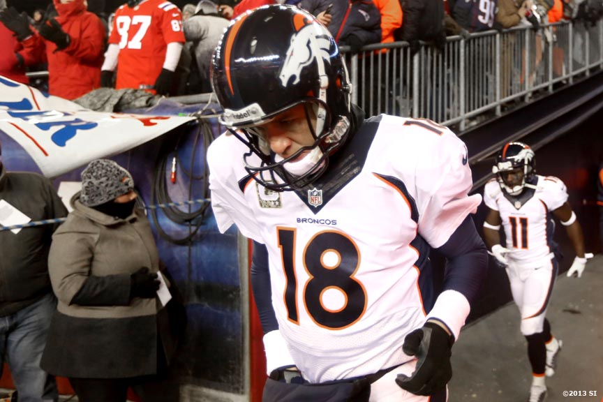 """Denver Broncos quarterback Peyton Manning walks onto the field before a game against the New England Patriots Sunday, November 24, 2013 at Gilette Stadium in Foxborough, Massachusetts."""