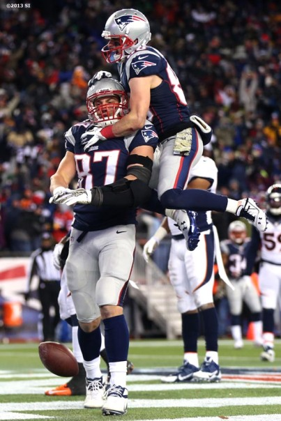 """New England Patriots wide receiver Danny Amendola jumps on tight end Rob Gronkowski after Gronkowski caught a touchdown pass during a game against the Denver Broncos Sunday, November 24, 2013 at Gillette Stadium in Foxborough, Massachusetts."""