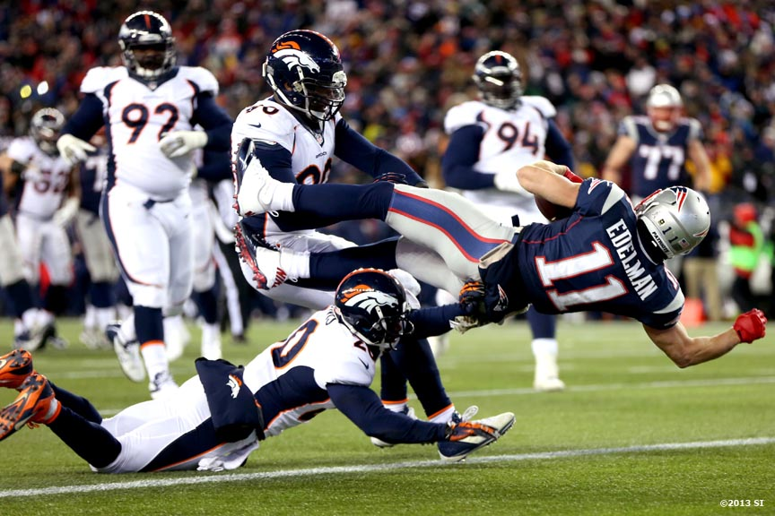 """New England Patriots wide receiver Julian Edelman dives toward the end zone as he scores a touchdown during a game against the Denver Broncos Sunday, November 24, 2013 at Gillette Stadium in Foxborough, Massachusetts."""