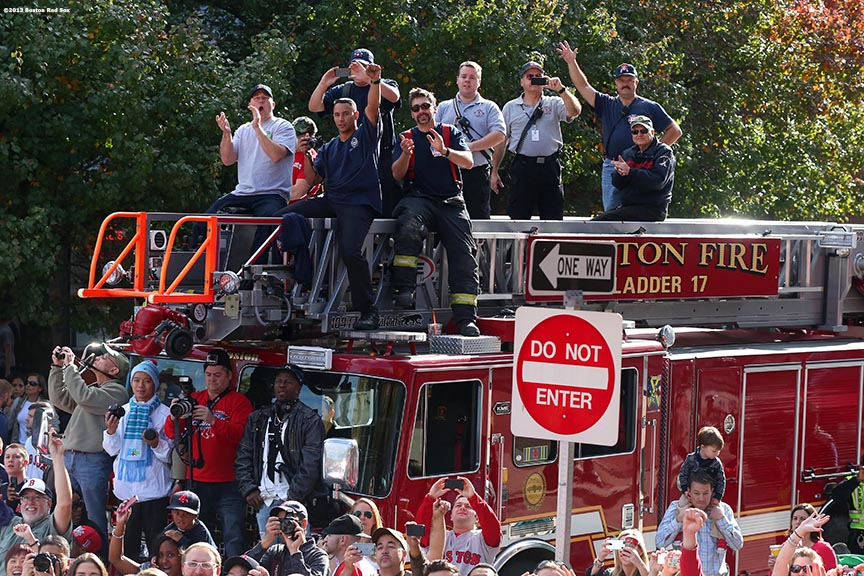 """Firefighters cheer along Boylston Street during the Rolling Rally World Series Championship Parade through downtown Boston, Massachusetts Saturday, November 2, 2013."""