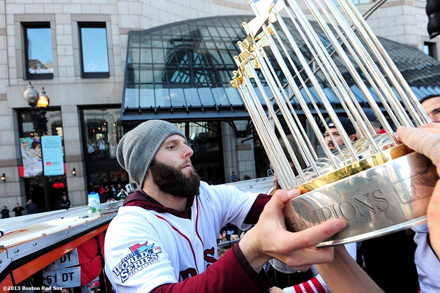 """""""Boston Red Sox second baseman Dustin Pedroia grabs the World Series trophy during the Rolling Rally World Series Championship Parade through downtown Boston, Massachusetts Saturday, November 2, 2013."""""""