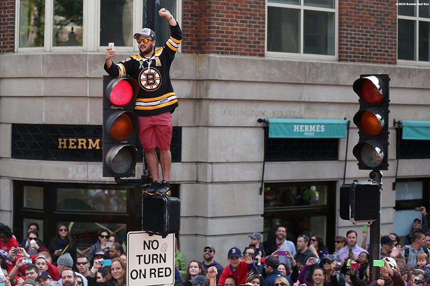 """A fan cheers atop a street light along Boylston Street during the Rolling Rally World Series Championship Parade through downtown Boston, Massachusetts Saturday, November 2, 2013."""