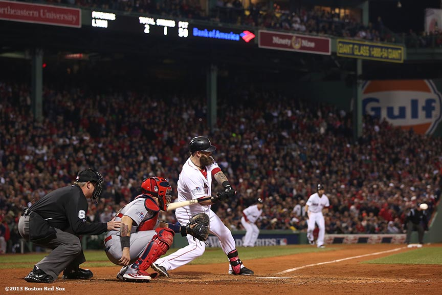 """Boston Red Sox first baseman Mike Napoli hits an RBI single during the fourth inning of game six of the 2013 World Series against the St. Louis Cardinals Wednesday, October 30, 2013 at Fenway Park in Boston, Massachusetts."""