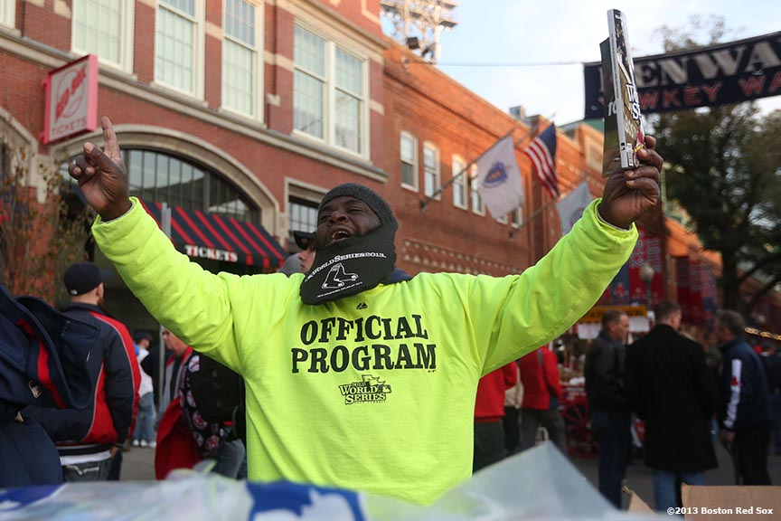 """A vendor sells programs on Yawkey Way before game six of the 2013 World Series between the Boston Red Sox and the St. Louis Cardinals Wednesday, October 30, 2013 at Fenway Park in Boston, Massachusetts."""