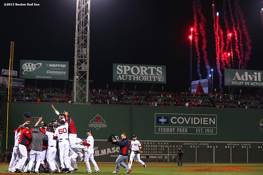 """Fireworks explode over the Green Monster as Boston Red Sox players celebrate after defeating the St. Louis Cardinals 6-1 to win the 2013 World Series Wednesday, October 30, 2013 at Fenway Park in Boston, Massachusetts."""