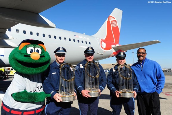 """Boston Red Sox mascot Wally the Green Monster, members of the Boston Police Department, and former Red Sox left fielder Jim Rice pose for a photograph on the runway during a Boston Red Sox visit to jetBlue Airways terminal at Logan Airport in Boston, Massachusetts Thursday, November 14, 2013 to unveil a 2013 World Series Championship banner."""