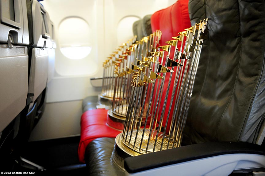 """The 2004, 2007, and 2013 World Series trophies are displayed across an aisle of seats on a jetBlue airplane during a Boston Red Sox visit to jetBlue Airways terminal at Logan Airport in Boston, Massachusetts Thursday, November 14, 2013 to unveil a 2013 World Series Championship banner."""