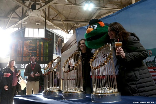 """Fans pose with Boston Red Sox mascot Wally the Green Monster and the 2004, 2007, and 2013 World Series trophies at South Station in Boston, Massachusetts Thursday, December 12, 2013 as part of the Red Sox Holiday Caravan to various locations throughout Boston."""