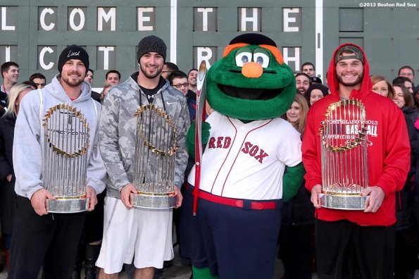 """Boston Red Sox pitcher Brandon Workman, catcher Ryan Lavarnway, mascot Wally the Green Monster, and pitcher Drake Britton pose for a photograph with the Olympic Torch and the 2004, 2007, and 2013 World Series trophies during an appearance to Fenway Park in Boston, Massachusetts Thursday, December 12, 2013."""