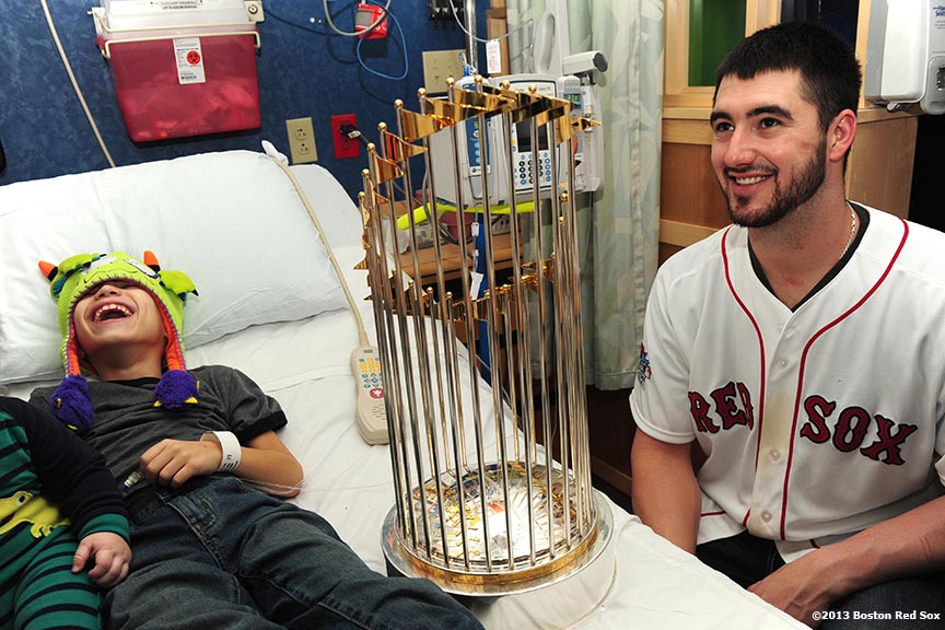 """Boston Red Sox pitcher Brandon Workman shares a laugh with a patient as he shows him the World Series trophy during a visit to The Jimmy Fund at Dana-Farber Cancer Institute in Boston, Massachusetts Friday, December 13, 2013 as part of the Red Sox Holiday Caravan to various locations throughout Boston."""