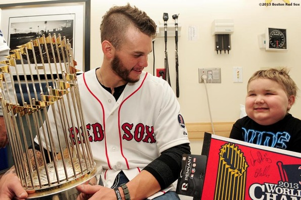 """Boston Red Sox pitcher Drake Britton shows the World Series trophy to a patient during a visit to The Jimmy Fund at Dana-Farber Cancer Institute in Boston, Massachusetts Friday, December 13, 2013 as part of the Red Sox Holiday Caravan to various locations throughout Boston."""