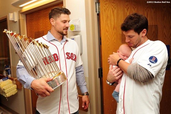 """Boston Red Sox pitcher Craig Breslow holds a baby as catcher Ryan Lavarnway holds the World Series trophy during a visit to Beth Israel Deaconess Medical Center in Boston, Massachusetts Friday, December 13, 2013 as part of the Red Sox Holiday Caravan to various locations throughout Boston."""