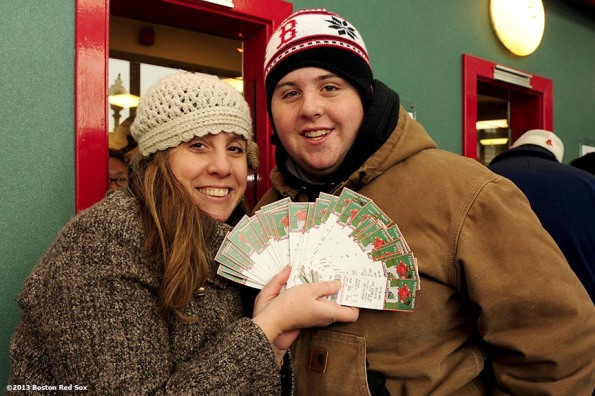 """Fans display tickets they purchased for the 2014 Boston Red Sox season during the annual Christmas at Fenway celebration Saturday, December 14, 2013, which featured speaking appearances and autograph sessions with players and coaches, holiday themed attractions and decorations, and opportunities for fans to purchase tickets for the 2014 season."""