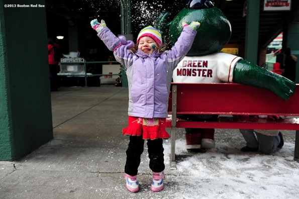 """Sienna Kaplan, 4, of Melrose, MA plays with snow during the annual Christmas at Fenway celebration Saturday, December 14, 2013, which featured speaking appearances and autograph sessions with players and coaches, holiday themed attractions and decorations, and opportunities for fans to purchase tickets for the 2014 season."""