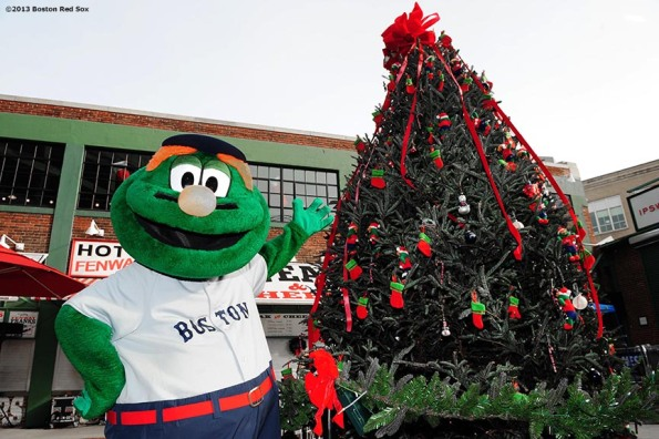 """Boston Red Sox mascot Wally the Green Monster poses with a christmas tree during the annual Christmas at Fenway celebration Saturday, December 14, 2013, which featured speaking appearances and autograph sessions with players and coaches, holiday themed attractions and decorations, and opportunities for fans to purchase tickets for the 2014 season."""