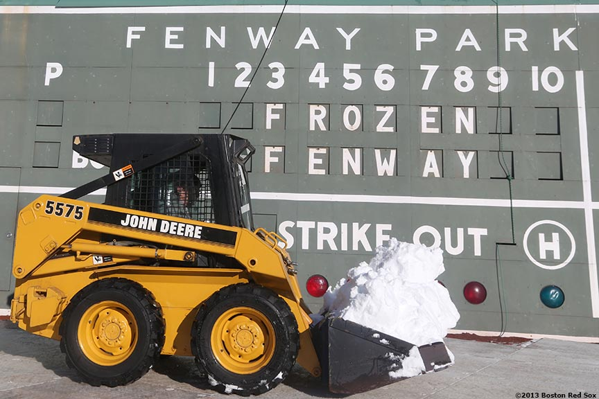 """A worker transfers snow in a tractor in front of the Green Monster scoreboard before the first day of Frozen Fenway 2014 at Fenway Park in Boston, Massachusetts Friday, December 27, 2013."""