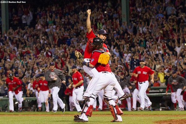 """Boston Red Sox teammates run out of the dugout in celebration as pitcher Koji Uehara and catcher Jarrod Saltalamacchia embrace after recording the final out of a 6-3 win over the Toronto Blue Jays to clinch the American League East title at Fenway Park Friday, September 23, 2013."""