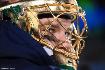 """A member of the Notre Dame hockey team looks on from the bench during a game against Boston College at Frozen Fenway 2014 Saturday, January 4, 2014 at Fenway Park in Boston, Massachusetts."""