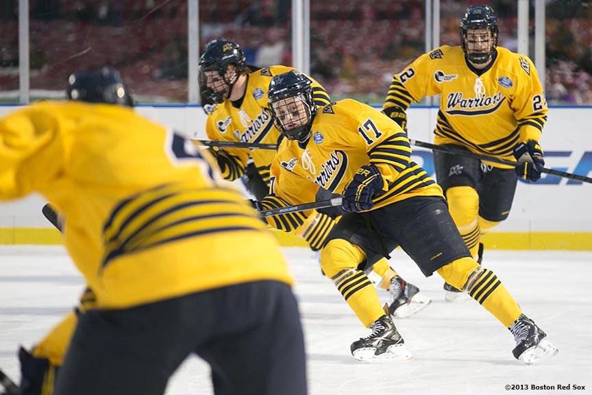 """Game action during the first period of a game between Providence College and Merrimack College at Frozen Fenway Saturday, January 4, 2014 at Fenway Park in Boston, Massachusetts."""