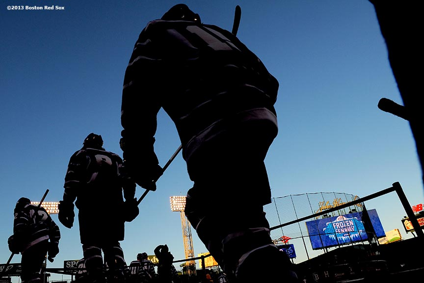 """University of Massachusetts players walk toward the ice before a game against Salem State at Frozen Fenway Tuesday, January 7, 2014 at Fenway Park in Boston, Massachusetts."""