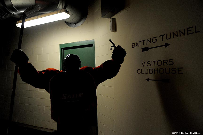 """A Salem State University player walk toward the batting tunnel between periods during a game against University of Massachusetts at Frozen Fenway Tuesday, January 7, 2014 at Fenway Park in Boston, Massachusetts."""