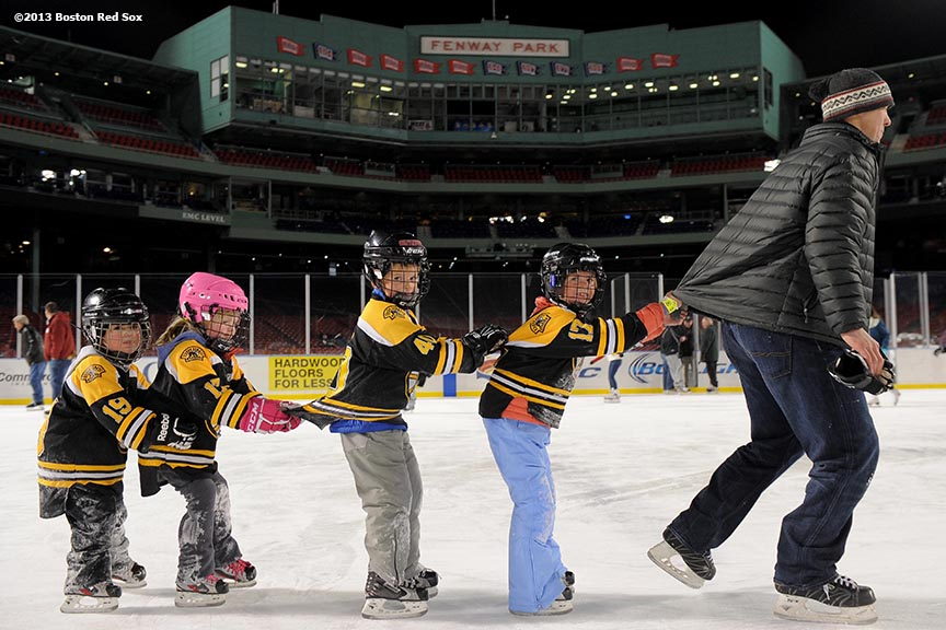 """A father leads his children in a lap around the rink at Fenway Park during a skate-around session with former Boston Bruins player Bobby Orr at Frozen Fenway Thursday, January 9, 2014 at Fenway Park in Boston, Massachusetts."""