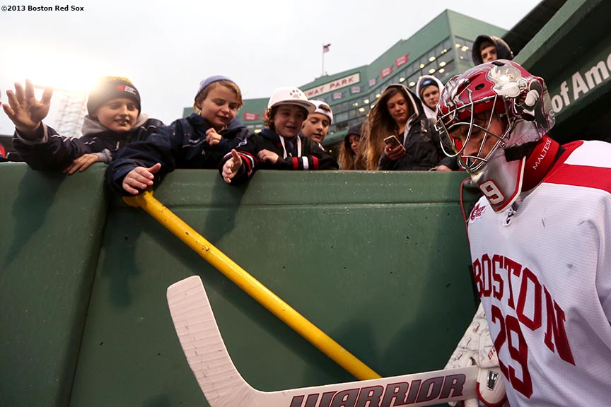 """A Boston University goalie walks through the dugout tunnel before a game against the University of Maine at Frozen Fenway Saturday, January 11, 2014 at Fenway Park in Boston, Massachusetts."""