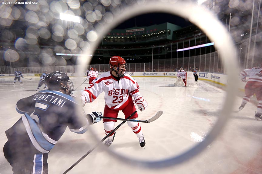 """Game action shown through a photographer's hole during a game between University of Maine and Boston University at Frozen Fenway Saturday, January 11, 2014 at Fenway Park in Boston, Massachusetts."""