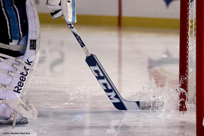 """A goalie pushes water off the ice with his stick after a rain delay during a game between University of Maine and Boston University at Frozen Fenway Saturday, January 11, 2014 at Fenway Park in Boston, Massachusetts."""
