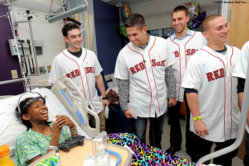 """Boston Red Sox rookies (left to right) Blake Swihart, Garin Cecchini, Christian Vazquez, and Matt Barnes laugh as they visit a patient at Boston Children's Hospital in Boston, Massachusetts Wednesday, January 15, 2014."""