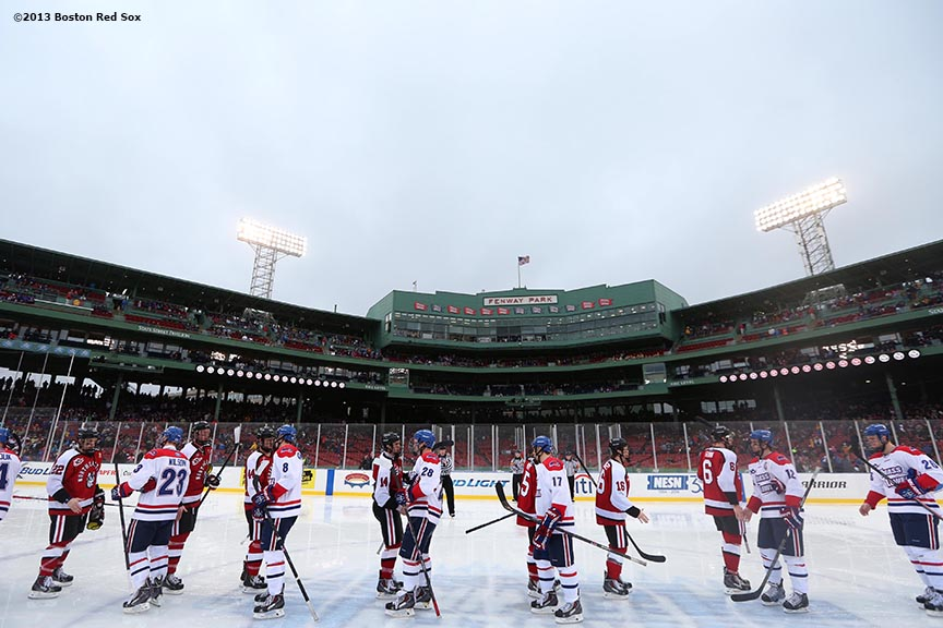 """University of Massachusetts Lowell players shake hands with Northeastern University players after a game Saturday, January 11, 2014 at Fenway Park in Boston, Massachusetts."""