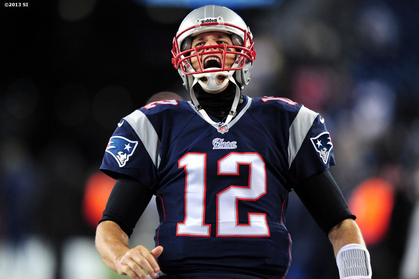 """New England Patriots quarterback Tom Brady yells as he warms up before a game against the Denver Broncos Sunday, November 24, 2013 at Gillette Stadium in Foxborough, Massachusetts."""
