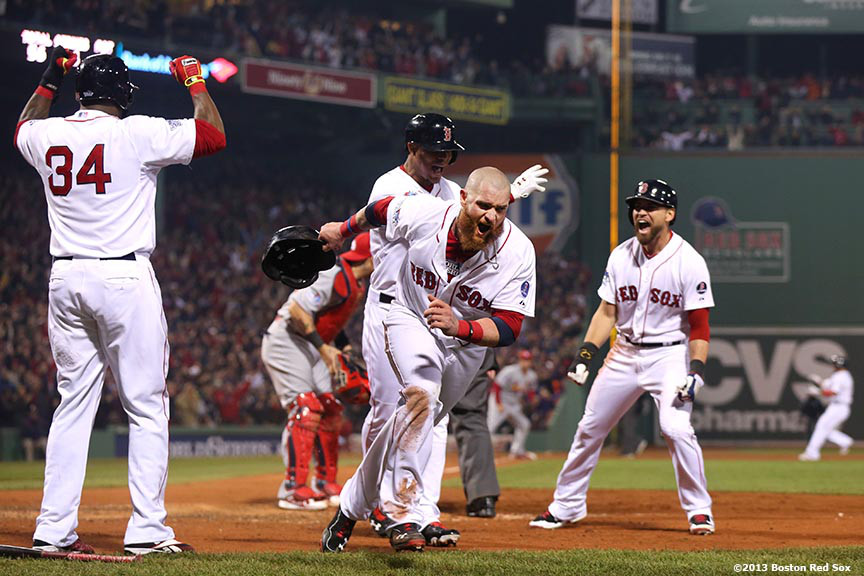 """Boston Red Sox left fielder Jonny Gomes celebrates alongside designated hitter David Ortiz, third baseman Xander Bogaerts, and center fielder Jacoby Ellsbury after scoring on an RBI double by right fielder Shane Victorino during the third inning of game six of the 2013 World Series against the St. Louis Cardinals Wednesday, October 30, 2013 at Fenway Park in Boston, Massachusetts."""