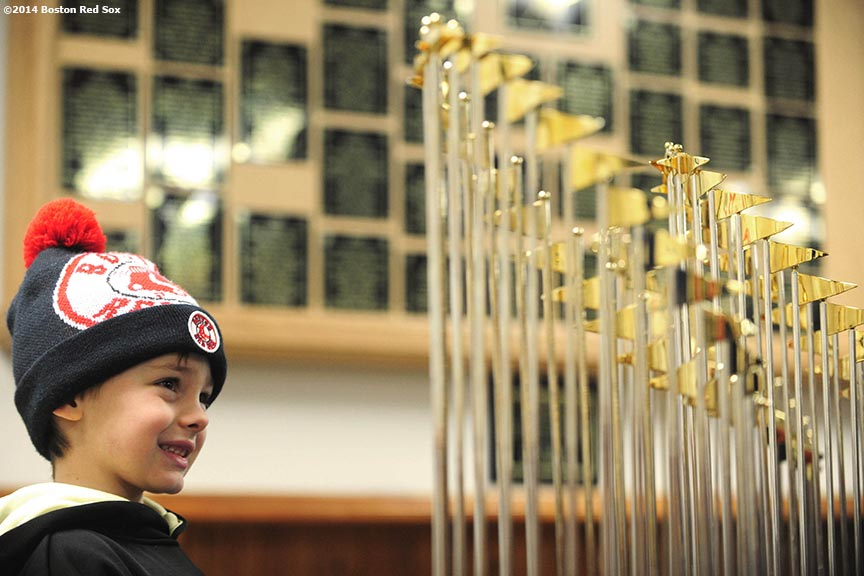 """A young fan poses with the 2004, 2007, and 2013 Boston Red Sox World Series trophies during an appearance at Hadlock Field, home of the Portland Sea Dogs, as part of a World Series trophy tour throughout Maine Saturday, January 25, 2014 in Portland, Maine."""