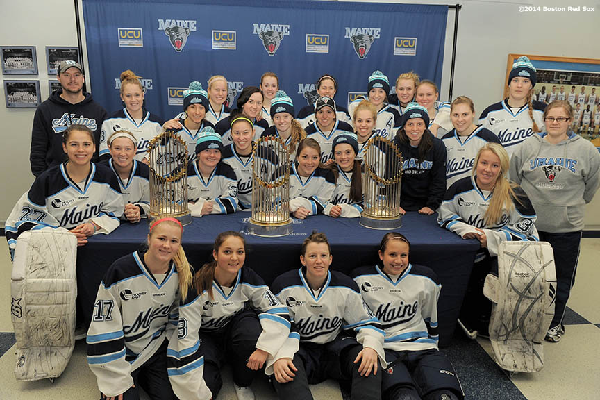 """The University of Maine women's hockey team poses with the 2004, 2007, and 2013 Boston Red Sox World Series trophies during an appearance at University of Maine's Alfond Arena in Orono, Maine Sunday, February 26, 2014 as part of a World Series trophy tour throughout Maine."""