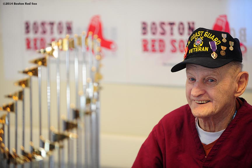 """A veteran poses with the 2013 Boston Red Sox World Series trophy during an appearance at the VA Hospital in Bedford, Massachusetts Wednesday, February 12, 2014 as part of the World Series trophy tour throughout Massachusetts."""