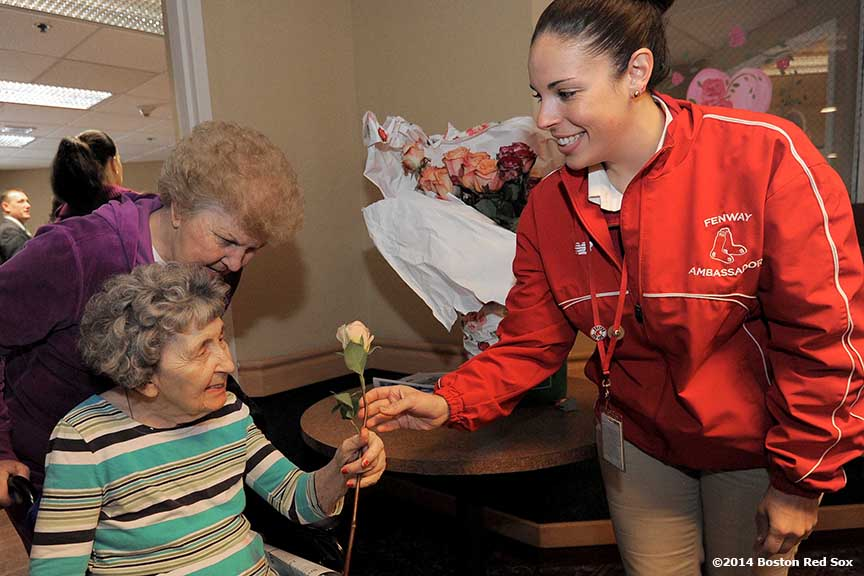 """Red Sox Ambassador Kali Richards (right) gives a rose to a resident at the Life Care Center of the North Shore in Lynn, Massachusetts Friday, February 14, 2014 during the Boston Red Sox Valentine's Day caravan and World Series trophy tour to various locations in Boston."""