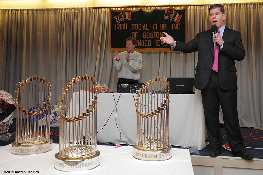 """Mayor Martin J. Walsh stands alongside the Boston Red Sox 2004, 2007, and 2013 World Series trophies as he addresses guests at the Irish Social Club in West Roxbury, Massachusetts Friday, February 14, 2014 during the Boston Red Sox Valentine's Day caravan and World Series trophy tour to various locations in Boston."""