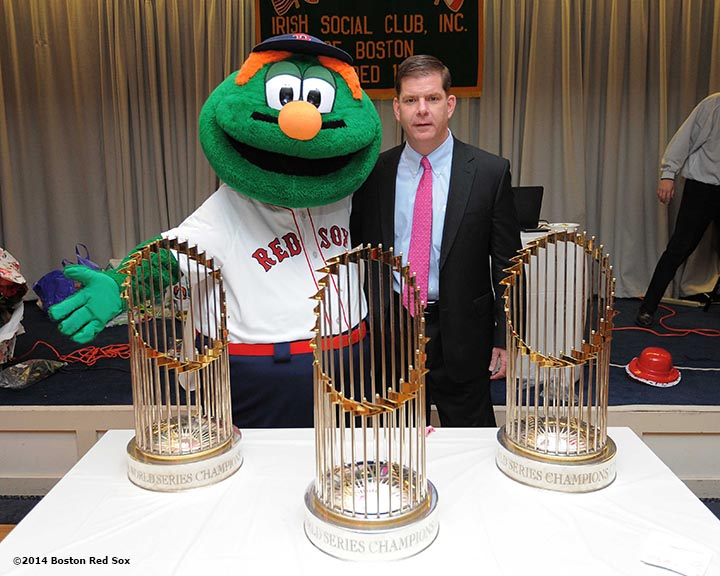 """Mayor Martin J. Walsh poses with Boston Red Sox mascot Wally the Green Monster and the 2004, 2007, and 2013 World Series trophies at the Irish Social Club in West Roxbury, Massachusetts Friday, February 14, 2014 during the Boston Red Sox Valentine's Day caravan and World Series trophy tour to various locations in Boston."""
