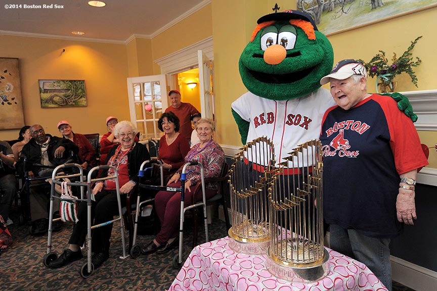 """Boston Red Sox mascot Wally the Green Monster poses with a resident alongside the 2004 and 2007 World Series at The Standish Village Assisted Living Center in West Roxbury, Massachusetts Friday, February 14, 2014 during the Boston Red Sox Valentine's Day caravan and World Series trophy tour to various locations in Boston."""