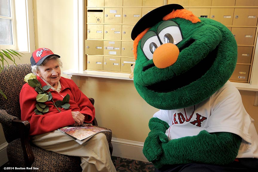 """Wally the Green Monster poses with a resident at The Standish Village Assisted Living Center in West Roxbury, Massachusetts pose alongside the 2004 and 2007 World Series trophies during the Boston Red Sox Valentine's Day caravan and World Series trophy tour to various locations in Boston Friday, February 14, 2014."""