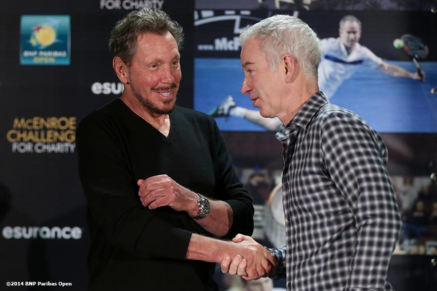 """BNP Paribas Open tournament owner Larry Ellison shakes hands with former player John McEnroe during the McEnroe Challenge for Charity VIP Draw Ceremony in the newly constructed Stadium 2 at the Indian Wells Tennis Garden in Palm Springs, California Friday, February 28, 2014."""