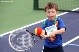 """A boy plays tennis during Kids Day at the Indian Wells Tennis Garden sponsored by the Coachella Valley National Junior Tennis and Learning Network Saturday, March 1, 2014 in Indian Wells, California."""