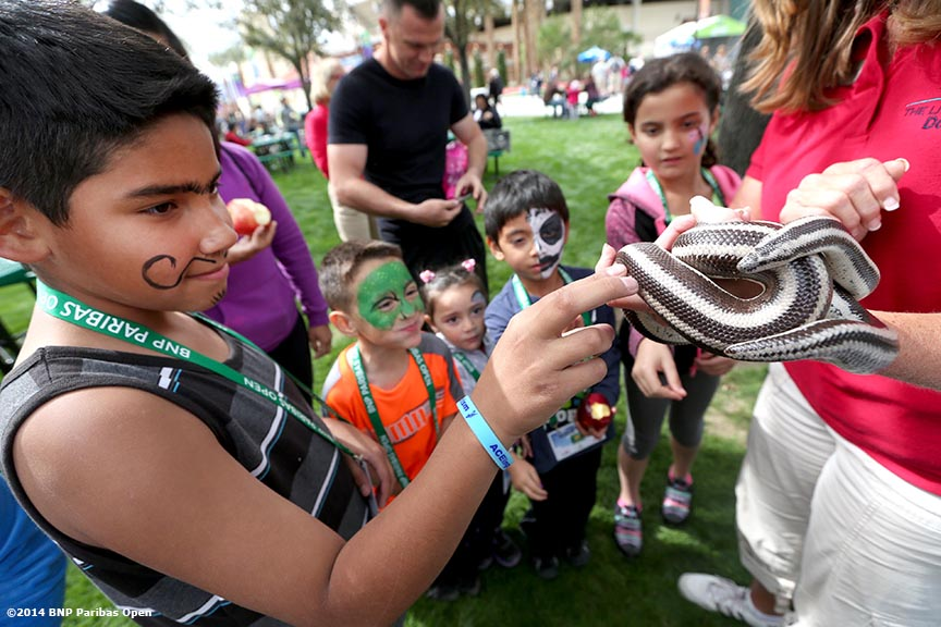 """""""Kids pet a snake at the petting zoo station during Kids Day at the Indian Wells Tennis Garden sponsored by the Coachella Valley National Junior Tennis and Learning Network Saturday,  March 1, 2014 in Indian Wells, California."""""""