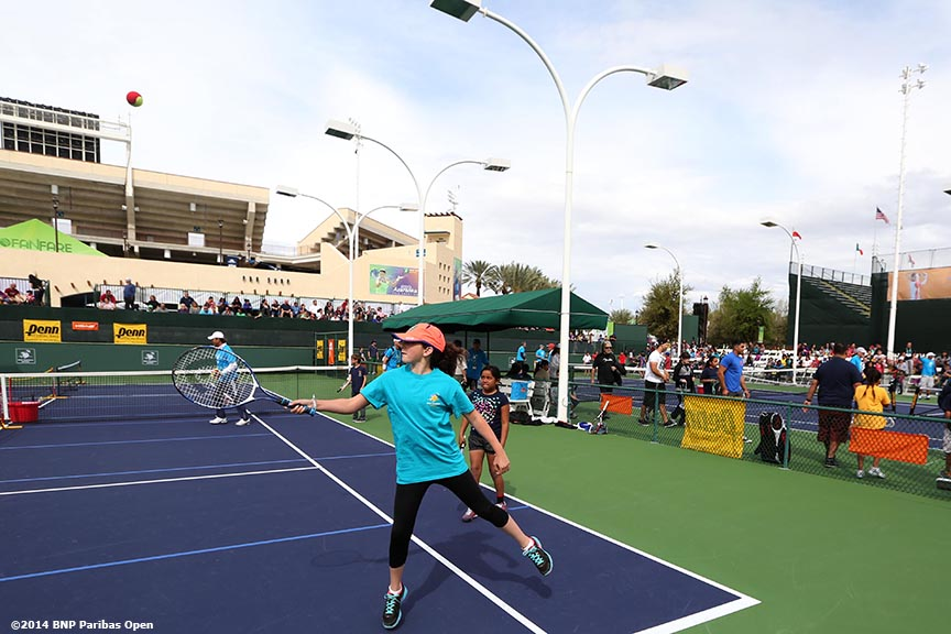 """Kids participate in a tennis clinic during Kids Day at the Indian Wells Tennis Garden sponsored by the Coachella Valley National Junior Tennis and Learning Network Saturday,  March 1, 2014 in Indian Wells, California."""