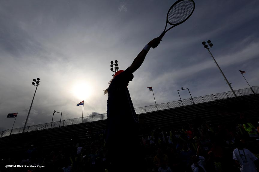"""""""An entertainer on stilts hits tennis balls into the crowd during Kids Day at the Indian Wells Tennis Garden sponsored by the Coachella Valley National Junior Tennis and Learning Network Saturday,  March 1, 2014 in Indian Wells, California."""""""