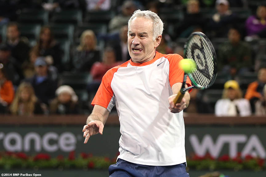 """John McEnroe hits a forehand during the McEnroe Challenge for Charity presented by Esurance Saturday,  March 1, 2014 in Indian Wells, California."""